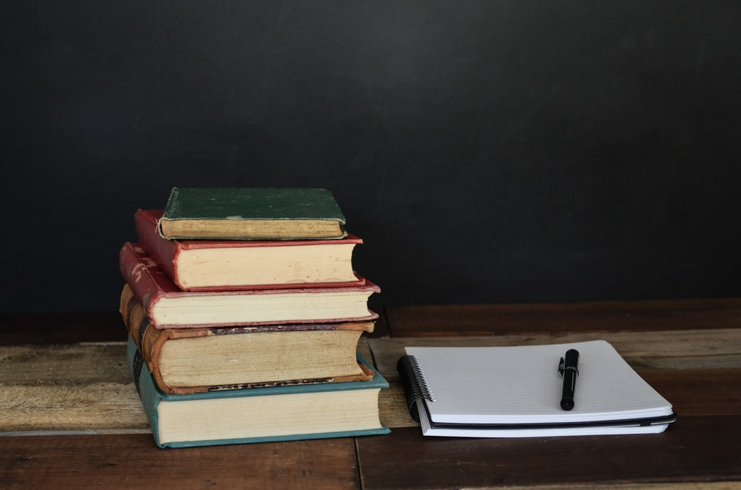 A desk with a pile of books and a notepad and pen.