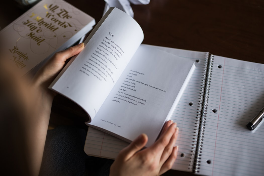 Woman reading poetry book with notepad and pen.