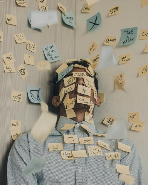 A man covered in post-it notes, all with writing on.