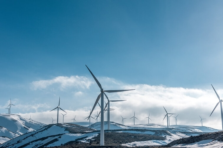 Wind turbines on a snow covered hill.
