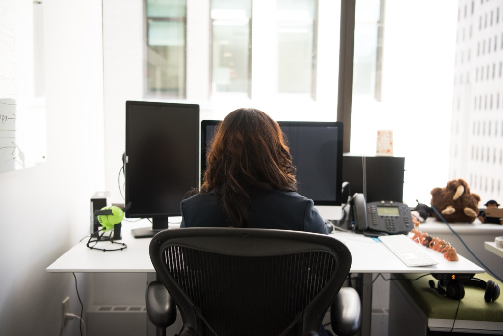 Woman sat in office chair at her desk