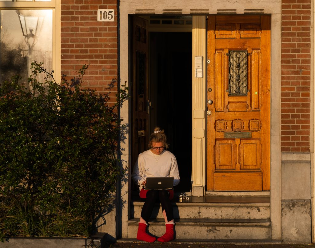 Woman working on laptop while sat on house steps